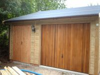 Single garage with a workshop on the side. Framed double doors and a cedar infill U&O door. With green felt roof.