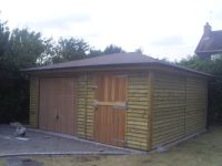 Garage in Feather Edge with a hipped roof to both sides, and a felt tile roof. Cedar U&O door, and a Cedar Personal Door.