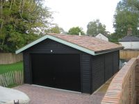 Feather Edge Garage, painted black with cedar shingles. Black Up & Over Door fitted to the front gable end.