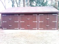 Triple garage with standard double doors and a brown felt tile roof. Customer stained the building chestnut.