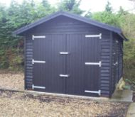 Single garage with feather edge cladding, painted in Ebony woodstain. Features Cedar shingle roof.