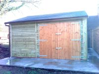 Wide single garage clad in feather edge boarding. Featuring felt tile roof and standard double doors.