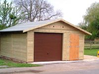 Wide single garage with a brown U&O door, and a personal door. Also with green mineral felt roof.