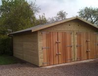 18 x18 Garage with Cedar framed double doors and a green felt roof.