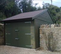10 x 18 Garage with felt tiles and green double doors. Doors are under the eaves.