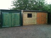 Low pitch single garage 16 x 16 with a set of double doors and a window. It is the building on the right hand side.