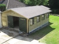 Large single garage with framed doors, and double glazed windows. Has an l-shaped workshop at the back.