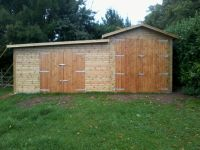 High sided garage at 3m to eaves for a large vehicle, with a lean to workshop to the side.