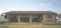 Quadruple garage with 3 openings to the front and a large window aperture.