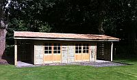 30 x 12 Building with cedar shingles and a log store to either side, with 9 pane double doors.