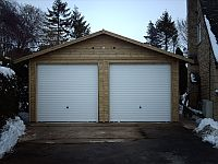Double Shiplap Clad Garage with a pair of White Metal Up & Over Doors