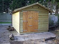 Single Shiplap Clad Garage with Double Doors set off to the left used to house a motorbike