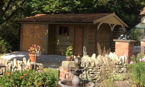 A lovely garage and workshop in a delightful garden. Featuring a recessed front and an extended Cart Lodge gable end.